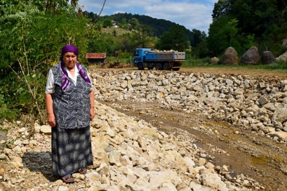 Dzemila stands on the banks of the stream.
