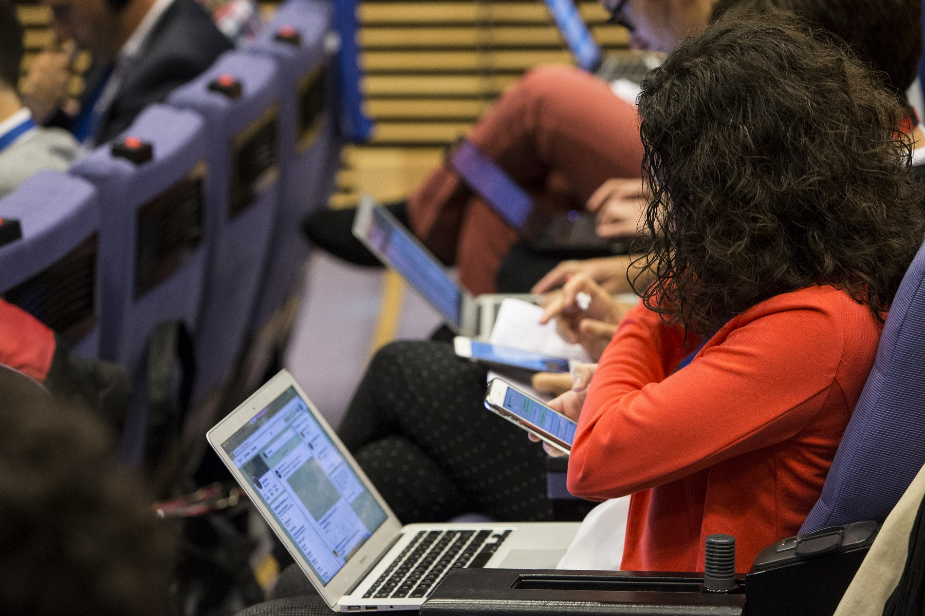 A journalist using her smartphone, with a laptop on her lap