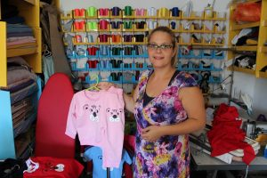 Dragica shows children's clothing made in her workshop